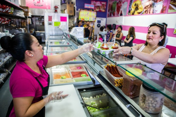 Rachel Rios reaches for her ice-cream orders from server Leticia Dominguez at La Michoacana as temperature reached 90 degrees in Riverside on Thursday, March 9, 2017. (Photo by Watchara Phomicinda, The Press-Enterprise/SCNG)