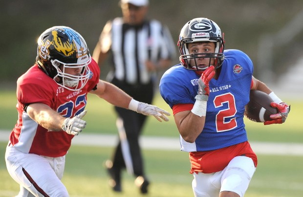 The North's Dylan Laurent scrambles for yardage after getting past the South's Ryan Hickey in the first quarter.The Orange County All-Star Classic high school football playing was played at Orange Coast College in Costa Mesa, CA on Friday, June 30, 2017. (Photo by Bill Alkofer,Orange County Register/SCNG)