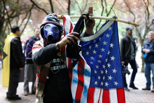 John Durano, who says he flew in from LA to participate and demonstrate his white pride, wears a gas mask and waves an American flag during a demonstration near City Hall and adjacent parks in Portland, Sunday, June 4, 2017. Crowds have swelled to several thousand as demonstrators from varying groups have converged in downtown Portland. (Beth Nakamura/The Oregonian via AP) ORG XMIT: ORPOR101