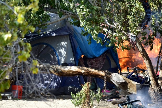 A homeless encampment was at the center of a fire in a San Bernardino wash Friday. -- Doug Saunders staff