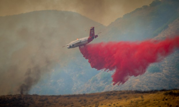 A firefighting aircraft drops fire retardant on a fast moving brush fire called the Bridge Fire near Green Spot road and the Santa Ana River basin in Highland, Friday, July 14, 2017. (Eric Reed/For The Sun/SCNG)