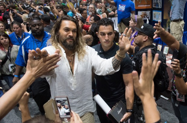 Jason Momoa, who plays Aquaman in the upcoming Justice League film, high-fives fans as he leaves the DC booth during day three of Comic-Con International at the San Diego Convention Center in San Diego, CA on Saturday, July 22, 2017. (Photo by Kevin Sullivan, Orange County Register/SCNG)