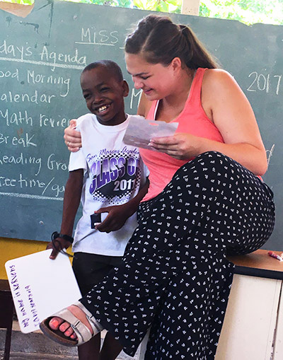 Cal State Fullerton student Abby Deming praises Kervens for a job well done while teaching in an orphanage school in Port-au-Prince, Haiti, this summer. (Photo courtesy of Cal State Fullerton)