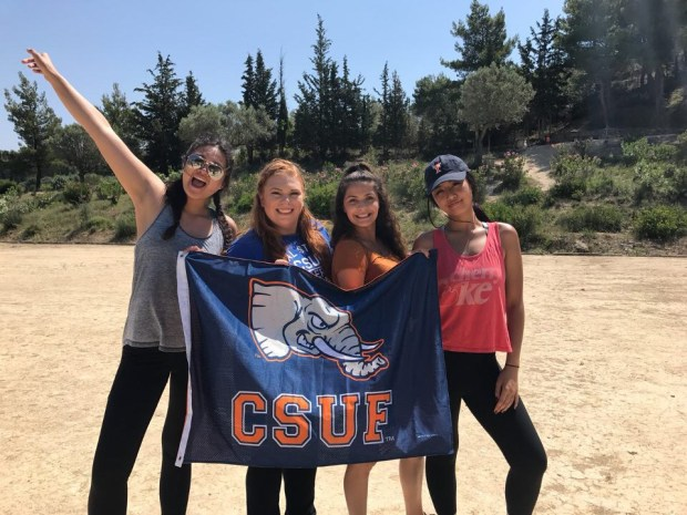 Cal State Fullerton students, from left, Julyana Amante, Samantha Richards, Talia Jankowska and Gabrielle Catipon hoist the colors in Greece. (Photo courtesy of Talia Jankowski)