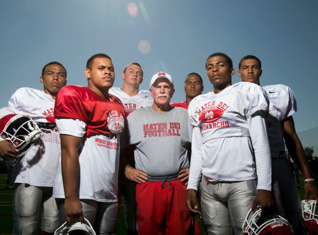 Wide receiver Amon-Ra St. Brown, defensive tackle Nathan Logoleo, offensive tackle Tommy Brown, head coach Bruce Rollinson, inside linebacker Solomon Tuliaupupu, wide receiver CJ Parks and wide receiver Bru McCoy, from left, help make Mater Dei football the No. 1 team in the O.C. Preseason Top 25 football rankings. Photographed in Santa Ana, CA on Friday, August 11, 2017. (Photo by Kevin Sullivan, Orange County Register/SCNG)