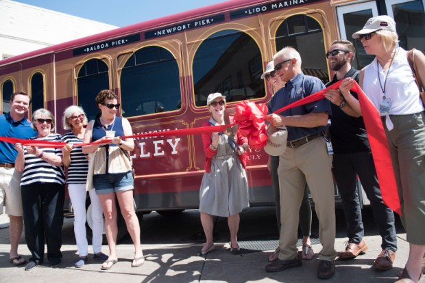 Newport Beach Councilwoman Diane Dixon cuts the ribbon during a ceremony unveiling the new Balboa Peninsula Trolley in Newport Beach, on Friday, June 16, 2017. (Photo by Nick Agro, Orange County Register/SCNG)