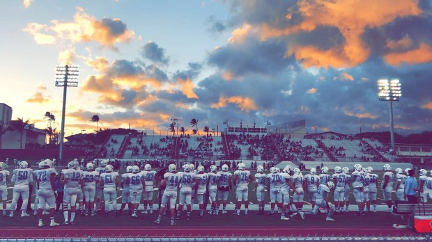 The Villa Park Spartan Football team enjoys a Hawaiian sunset, and a victory in the first game against Damien Memorial on Oahu. (Courtesy of Spartan Football)
