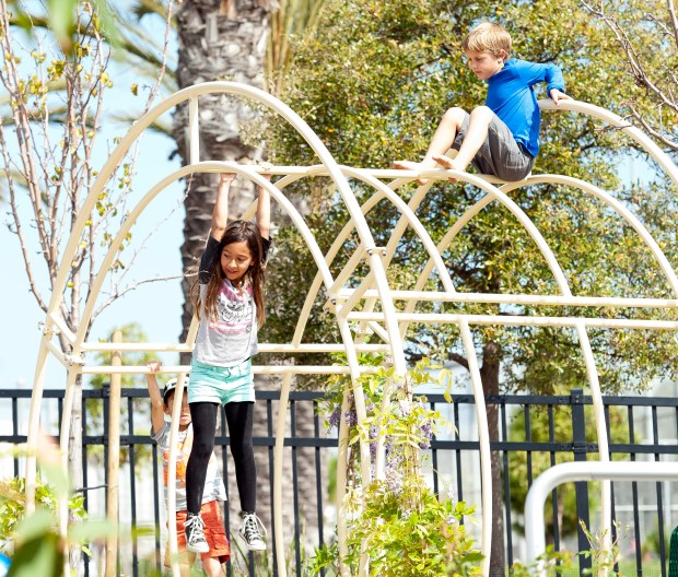 Hanging out on the climbing bars, Tessa Arciniega, 7, and Merek Amziarz, 6, both of San Clemente, on Saturday.///ADDITIONAL INFO: 09.spn.courtneys.0327.db.jpg -- 3/21/15 -- PHOTO BY DAVID BRO, CONTRIBUTING PHOTOGRAPHER----Courtney's Sandcastle, a universal access playground at Vista Hermosa Sports Park in San Clemente, has completed phase two adding a tide pool, sensory garden and climbing bars as part of the project's latest fundraising effort.