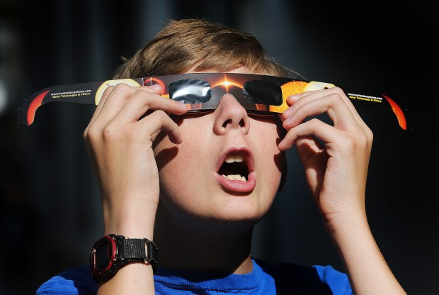 Colton Hammer tries out his new eclipse glasses he just bought from the Clark Planetarium in Salt Lake City in preparation for the Aug. 21 eclipse. Eye doctors urge strict adult supervision for eclipse watchers under 16 years old.