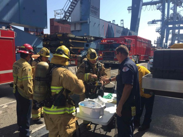 Long Beach firefighters gather at Pier G, after boarding a ship in the Port of Long Beach, Sunday, Aug. 6, 2017. Long Beach firefighters treated 11 workers and one firefighter for exposure to some hazardous material fumes where a flammable liquid leaked from a 6,000 gallon tank on a container vessel. Two persons have been taken to a hospital. (Photo by Brian Fisk/Long Beach Fire Department via AP)