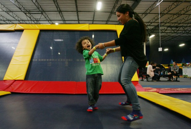 ABA therapist Jocelyn Flores, encourages Lucas Mora, 4, of Ontario, to jump with her as the two play during a day for children with special needs on Thursday, Oct. 13, 2016, at Sky High Sports Trampoline Park in Jurupa Valley. Autism Speaks held a kick off party on Thursday and the proceeds from every pair of jump socks purchased at the trampoline park will be donated to the organization. (Stan Lim, The Press-Enterprise/SCNG)