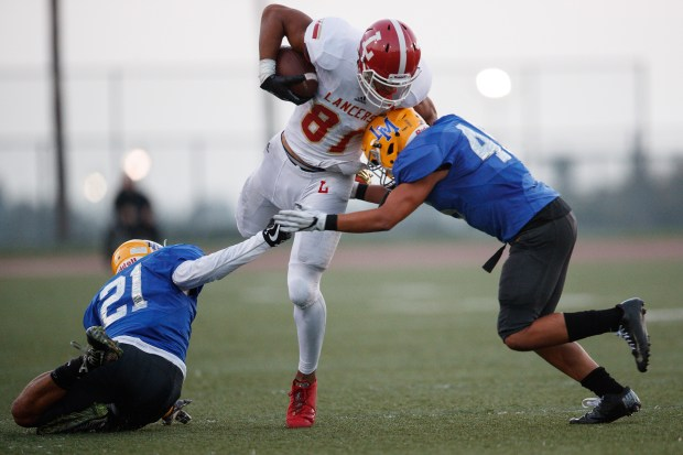 Orange Lutheran's Kyle Ford (81) breaks a tackle attempt by La Mirada's Maximus Ahoia (21) and Justin Diebert (45) after completing a reception during the first half of a prep football game at La Mirada High School in La Mirada, Calif. on Friday August 25, 2017. (Photo by contributor Raul Romero Jr)