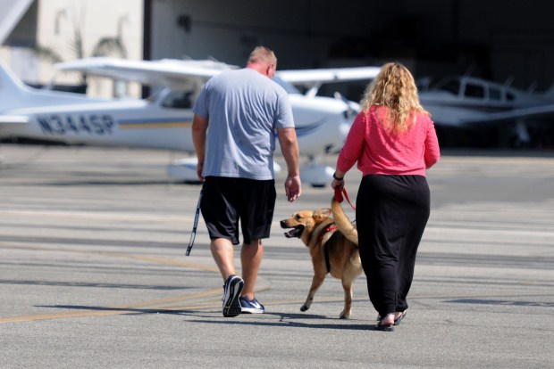 Scott and Shellie Bibee leave the airport with Emery after she was flown from Corpus Christi by pilot Brett James, a volunteer with Pilots N Paws who has flown 56 dogs to safety. Emery will live with the Bibees in Mission Viejo until she can be reunited with Shellie's son Cameron, her owner. (Photo by Dean Musgrove, Los Angeles Daily News/SCNG)