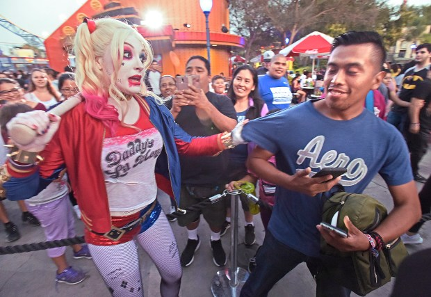 Suicide Squad character Harley Quinn, left, grabs Jorge Garcia of Los Angeles to pose for a photo during the Six Flags Fright Fest Opening Night at Six Flags Magic Mountain in Valencia on Saturday, Sept. 16, 2017. (By Dan Watson. Contributing Photographer, Los Angeles Daily News/SCNG)