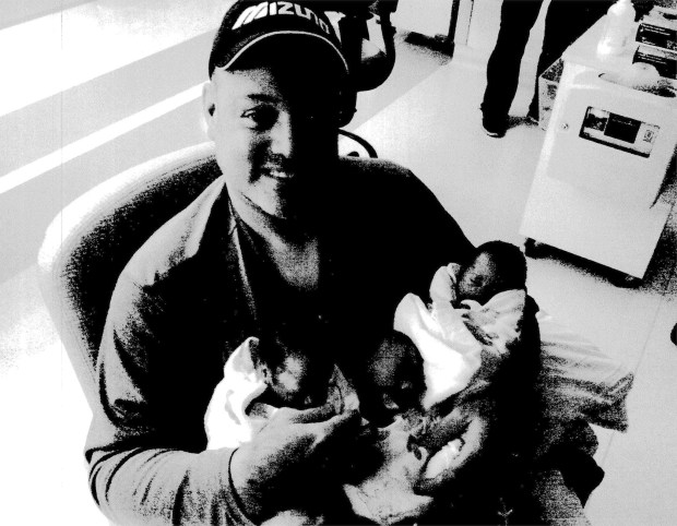 A photocopied image of Chester Shannon Moore Jr., with his triplets. (Image via L.A. Superior Court document)