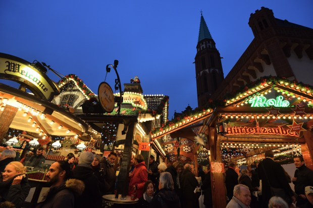 FRANKFURT/MAIN, GERMANY - NOVEMBER 26: Visitors walk through the Christmas market at Roemerberg square on its opening day on November 26, 2014 in Frankfurt, Germany. Christmas markets, which traditionally sell mulled wine, stollen cake, Christmas tree ornaments and other crafts and are an essential part of German Christmas tradition, open across the country this week. (Photo by Thomas Lohnes/Getty Images)