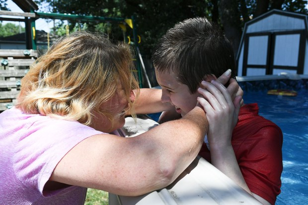 Debbie Cordone embraces her son, James, who she said benefited tremendously from intensive behavioral therapy at the Kennedy Krieger Institute in Baltimore. (Nancy J. Parisi for KHN)