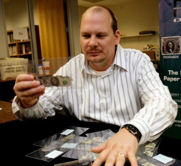 """Brian Ingram examines some """"D.B.Cooper cash"""" at Collectors Universe Tuesday Feb. 12, 2008 in Santa Ana, Calif. Ingram, from Arkansas, found the sole link to the only unsolved airline hijacking in U.S. history buried along the Columbia River during a family vacation in 1980. Ingram brought the recovered money to Collectors Universe to be authenticated, certified and preserved. Now, Ingram hopes to auction the weathered bundle of $20 bills as the FBI launches a new effort to find the unknown hijacker who parachuted into the night after taking over the 1971 Northwest Orient Airlines flight. (AP Photo/Nick Ut)"""