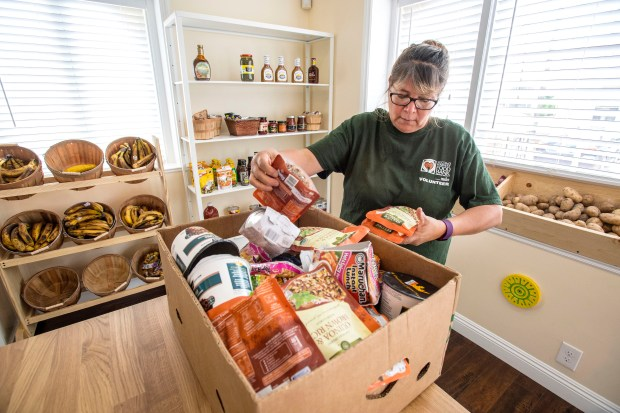 Marta Gomez, a volunteer at the Mercado El Sol, a food pantry opened by Second Harvest Food Bank, near downtown Santa Ana, restocks the shelves in between shoppers on Thursday, June 8, 2017. The pantry serves low-income families in the surrounding neighborhood, (Photo by Mark Rightmire, Orange County Register/SCNG)