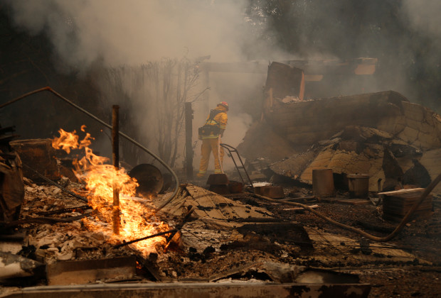 A Palo Alto firefighter puts out a hotspot off in Santa Rosa in October. (Nhat V. Meyer/Bay Area News Group)