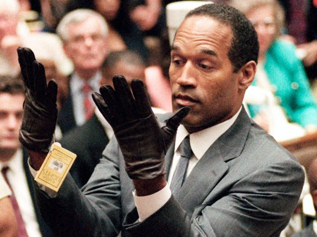 In this June 21, 1995, file photo, O.J. Simpson holds up his hands before the jury after putting on a new pair of gloves similar to the infamous bloody gloves during his double-murder trial in Los Angeles. (AP Photo/Vince Bucci, Pool, File)