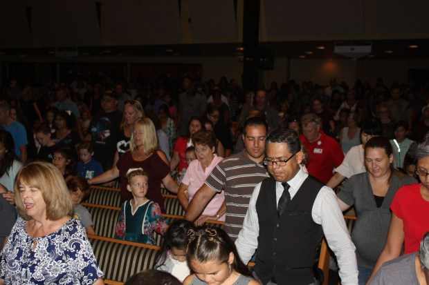 Parents and students at Riverside's Harvest Christian School pray together as they launch the new school year.Photo courtesy of Harvest Christian School