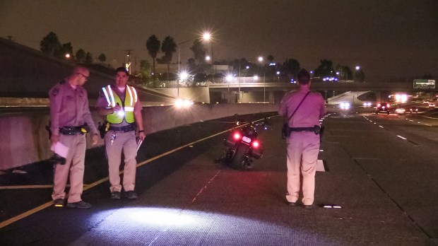 California Highway Patrol officers investigate the scene of an accident where a 64-year-old Orange man died on the 55-freeway near Main Street in Tustin on Saturday, September 30, 2017 after his Harley Davidson hit the rear of a Freightliner tour bus causing him massive head trauma. The deceased man was identifed as Loren Love, 64, of Orange. (Photo by Southern Counties News)