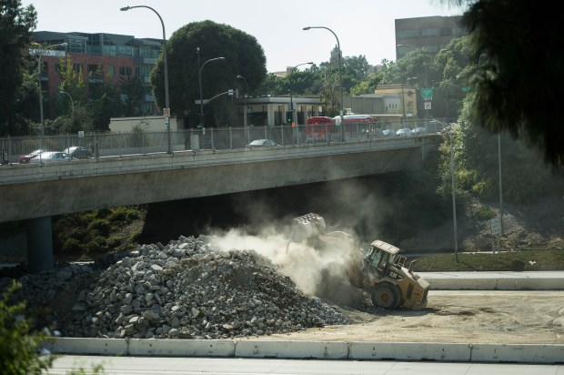 A bulldozer works on a growing pile of broken concrete on the North 710 Freeway stub in Pasadena on Monday, Oct. 2, 2017. The piles of broken concrete from the 210 repaving project are being recycled at the temporary cement plant back into 210 Freeway. Many Pasadenans are unhappy with the portable plant. (Photo by Sarah Reingewirtz, Pasadena Star-News/SCNG)