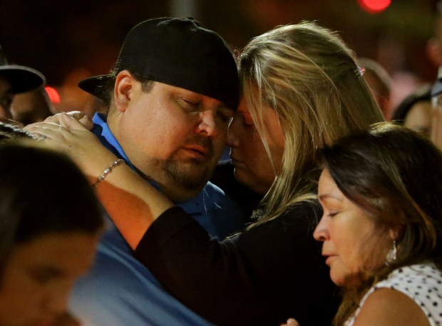 Jonathan Mulligan, 36, of Chino Hills and wife Elizabeth attended the concert with friends Rocio Rocha Guillen, 40, and fianceŽ, Chris Jaksha as they comfort one another during candle light vigil at Roosevelt High School on Thursday, Oct. 5, in Eastvale. (Photo by Terry Pierson, The Press-Enterprise/SCNG)