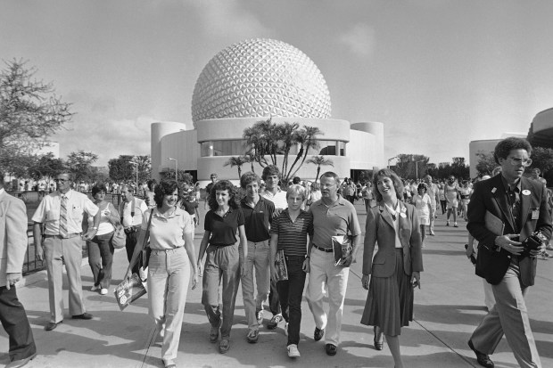 The Cason family, the first family to enter EPCOT Center, walk into the park after leaving the Spaceship Earth in Lake Buena Vista, Florida on Oct. 1, 1982. (File photo by Doug Jennings, The Associated Press)