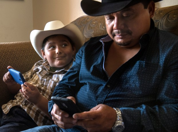 Hugo Secundino still struggles with the pain of losing his 14-year-old son, Angel, to gang violence in 2006. He recognizes mistakes he made with Angel and now wants to be a better, more attentive parent to his children, he says. A bull rider himself, he watches bull riding videos with his 7-year-old son on Saturday, July 29, 2017. (Photo by Mindy Schauer, Orange County Register/SCNG)