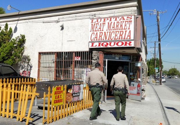 Sheriff's Deputy's head in to Lupita's Market to oversee closing of business.The Health Department shut down LupitaÕs Family Restaurant in Carson today, after its employees and landlord took over the restaurant without the ownerÕs permission when he got too sick to maintain the business.Photo by Robert Casillas, Daily Breeze/SCNG