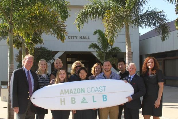 City officials from Huntington Beach gathered around the surfboard they are delivering to Amazon as part of a joint bid with Long Beach to become a home to a second national headquarters for the retail giant (Photo courtesy City of Huntington Beach)