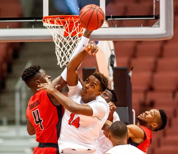 Cal State Fullerton guard Khalil Ahmad, center, rejects a shot by Cal State Northridge forward Tavrion Dawson, left, during the quarterfinal game of the Big West Tournament in Anaheim on March 9. (Photo by Paul Rodriguez, Orange County Register/SCNG)