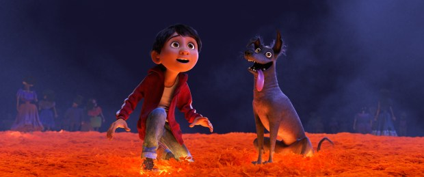 """In Disney/Pixar's """"Coco,""""Miguel desperately wants to prove hismusicaltalent. But when he strums the guitar ofhis idol, the late Ernesto de la Cruz, Miguel sets off a mysterious chain of events and finds himself — and his loyal dog Dante — crossing into the Land of the Dead via a breathtaking bridgemadeof marigoldpetals.(Image courtesy of Disney/Pixar)"""
