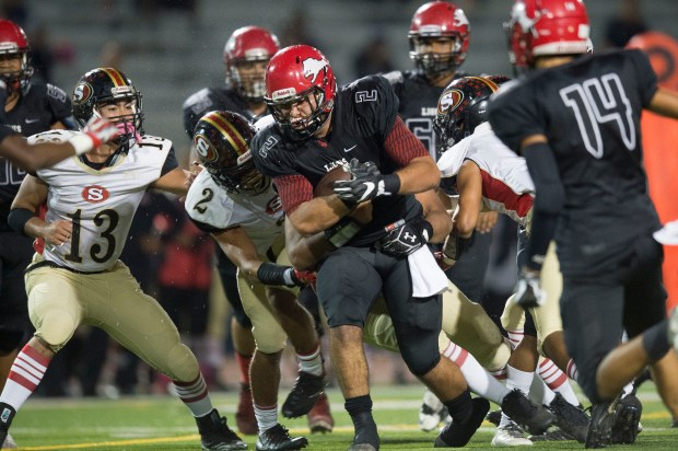 Westminster's Jacob McGookin grinds through a gang of Segerstrom's tacklers including Keith Morales during a Golden West league game at Westminster High School in Westminster on Thursday, October 26, 2017. (Photo by Matt Masin, Orange County Register, SCNG)