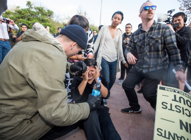 A protester falls to the ground after being hit by pepper spay when pro- and anti-Milo Yiannopoulos demonstrators clashed outside Titan Student Union in Fullerton on Tuesday, October 31, 2017. (Photo by Leonard Ortiz, Orange County Register/SCNG)