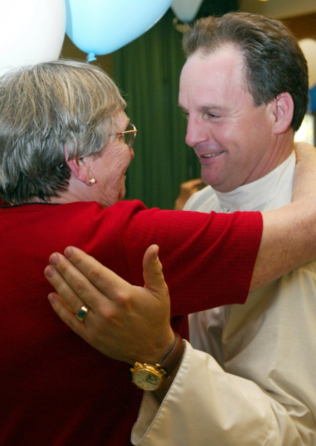 Parishoner Kay Baker, 81, of Covina, left, hugs Father Chris Cunningham, of Covina, at his final farewell Wednesday (March 10, 2004) at St. Louise de Marillac Catholic Church in Covina. Cunningham has been removed as pastor for the church by the Archdiocese of Los Angeles.(Photo by Jennifer Cappuccio/Freelancer/SVCITY)