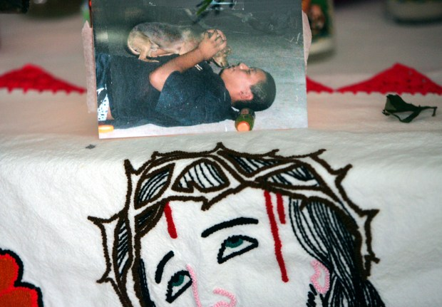 In 2006 a shrine in the living room of Hugo Secundino pays tribute to his slain son Angel, pictured at top. (Eugene Garcia, Register File)