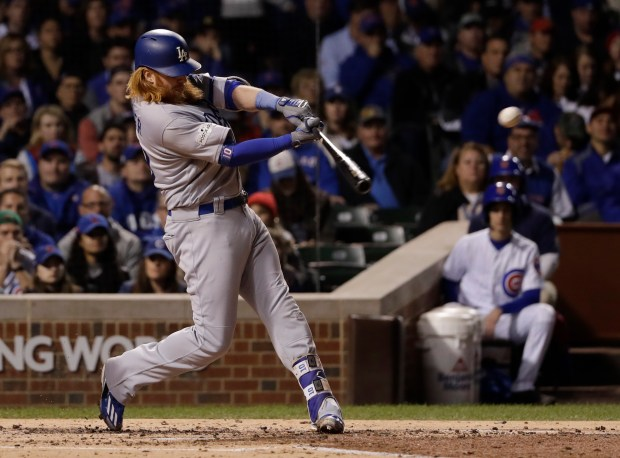 Los Angeles Dodgers' Justin Turner hits an RBI single during the third inning of Game 5 of the NLCS on Thursday night in Chicago. Turner shared NLCS co-MVP honors with Chris Taylor. (AP Photo/Matt Slocum)
