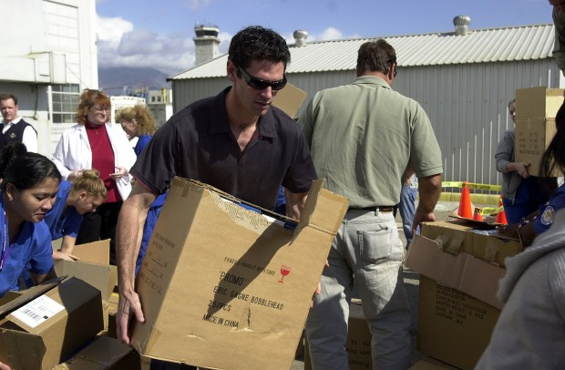 Shawn Green, then an outfielder for the Los Angeles Dodgers, hauls boxes Oct. 30, 2003, outside the shelter set up by the Red Cross at the San Bernardino International airport in San Bernardino as he, coach Glenn Hoffman and manager Jim Tracy paid a visit to the people staying at the shelter, signing autographs and handing out blankets and souvenirs. About 2,000 people were evacuated from their homes because of the Old Fire in 2003. (File photo by Valerie Berta, The Press-Enterprise/SCNG)