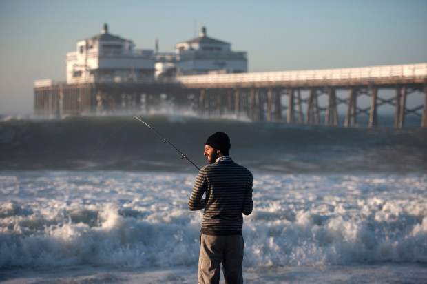 Gevorg Ghaplanyan, of Los Angeles, tries to fish as big waves hit the pier at Surfrider Beach in Malibu in August 2014. //ADDITIONAL INFORMATION: lar.bigwaves.0828 Ð 08/27/14 Ð ED CRISOSTOMO, ORANGE COUNTY REGISTER- Ed starting at Surfrider beach in Malibu where a surfer was pulled from the water Tuesday. Big waves start to hit the west coast of California on Wednesday.