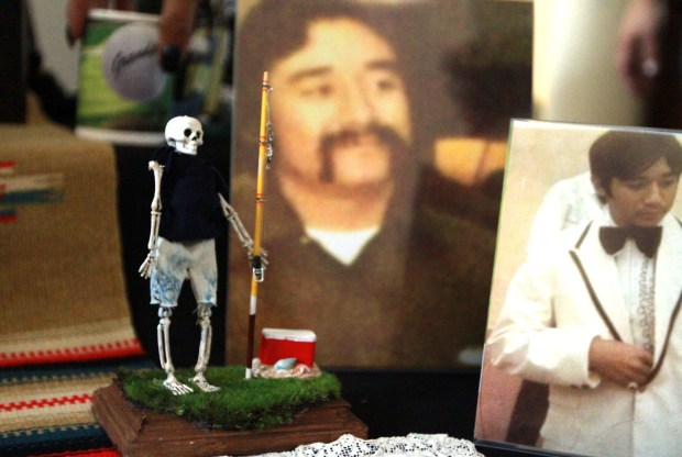 A fisherman figurine build by Christina Arellano, 42, of Riverside, sits near photos of Joe Melendez on an altar on Thursday, November 2, 2017 at her home in Riverside, Ca. Arellano has built an altar and participated in Riverside's Dia de los Muertos event every year for 12 years. (Micah Escamilla/Correspondent)