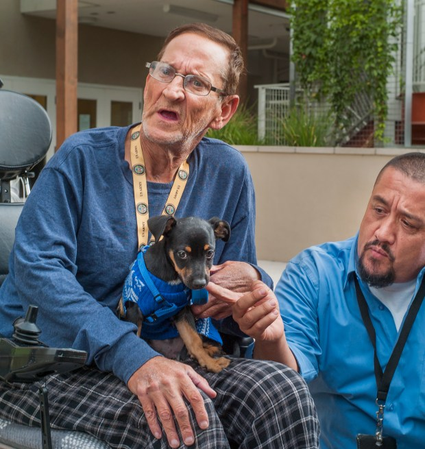 Richard Ross, a Veteran with his newly adopted dog discussing health issues. Santiago Reyes, Team Leader, Pasadena Housing Works, makes friends with the puppy at T Bailey Apartments in Eagle Rock Friday, Nov. 3, 2017. LA County leaders have passed a flurry of motions and raised many discussions on how to improve care among people with mental illnesses, especially the most vulnerable. (Photo by Walt Mancini/Pasadena Star-News/SCNG)