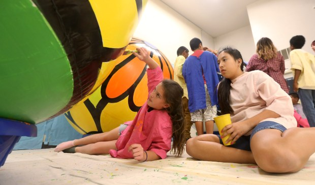 6th graders Madison McHugh, 11, left, and Camila Nuñuz, 11, take turns painting a sphere on Thursday, Nov. 2, 2017 at Pachappa Elementary School in Riverside. Students from area schools are hand-painting spheres that will float in Lake Evans for a three-week festival. The project is a fundraiser for the Riverside Art Museum, with businesses or community members sponsoring each sphere for $350.(Stan Lim, The Press-Enterprise/SCNG)