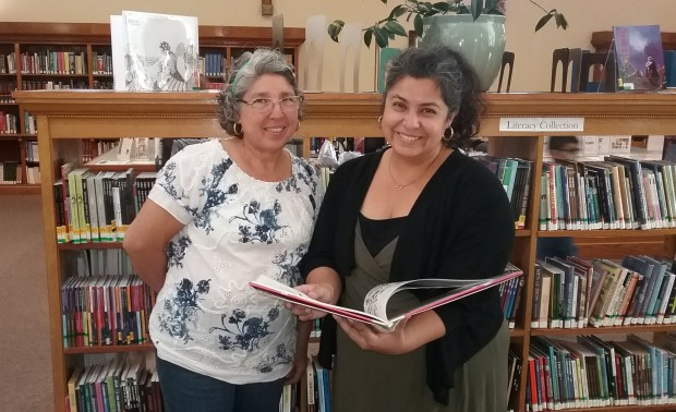 Maria Hernandez, left, and her Redlands Adult Literacy Program tutor Catrina Choudhry, right, look at a new book provided by donations to the literacy program. (Courtesy Photo)