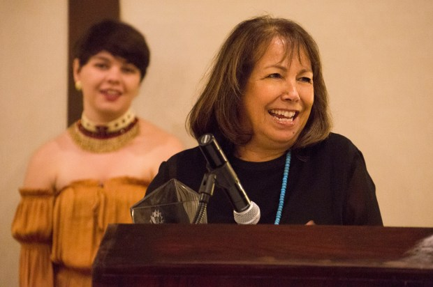 Vicki Vasques accepts the Native American Alumni Recognition Award at the Native American Heritage Month reception on Nov. 8 at the Fullerton Marriott. Raven Bennett-Burns, president of the Inter-Tribal Student Council, stands in the background. (Photo courtesy of Cal State Fullerton)