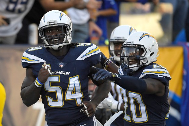 Los Angeles Chargers outside linebacker Melvin Ingram, left, celebrates with defensive back Desmond King after picking up a fumble and running it in for a touchdown against the Buffalo Bills during Sunday, Nov. 19, 2017, in Carson. The Chargers are playing the Dallas Cowboys on Thanksgiving Day, and Dish Network subscribers might not be able to see the game on the satellite network. (AP Photo/Mark J. Terrill)