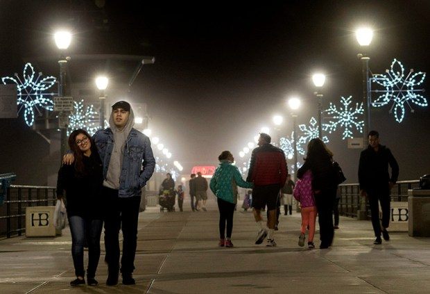 "The Huntington Beach Pier was a place for romance as couples walk alongside 81 lit giant snowflakes during last years' ""Light a Light of Love."" (Photo by Cindy Yamanaka, Orange County Register/SCNG)"