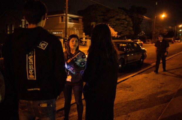 MET team psychiatric social worker Kristal Ramirez speaks to the friends of a suicidal young woman who was in a patrol car on a Temple City street. (Photo by Sarah Reingewirtz, Los Angeles Daily News/SCNG)